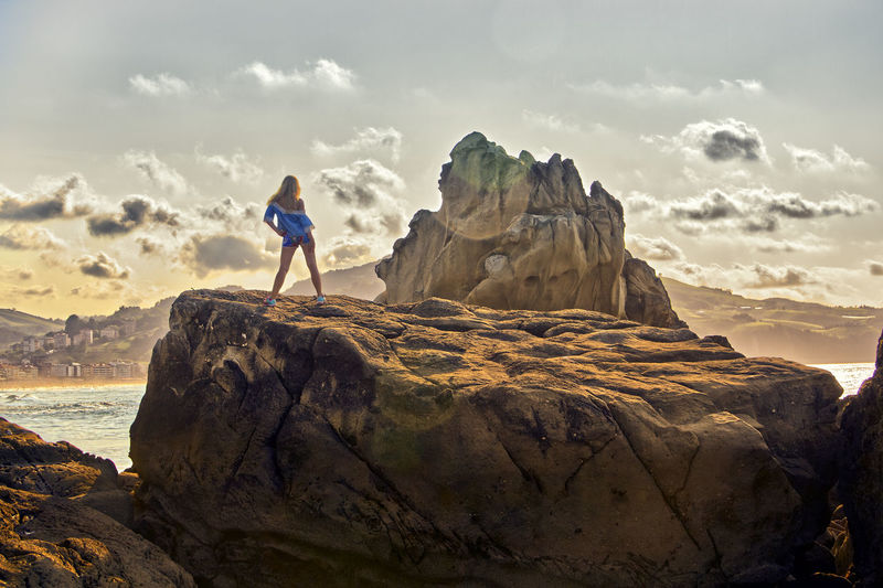 Rear view of mid adult woman standing on rock against sky during sunset