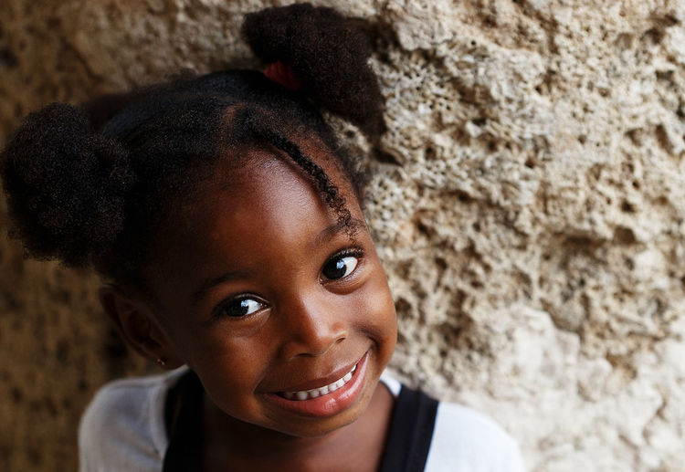 Close-up portrait of cute smiling girl against wall