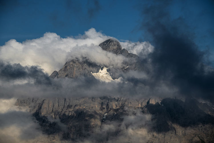 Scenic view of mountain emerging from clouds