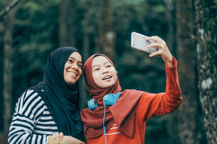 Smiling friends wearing hijab while taking selfie through mobile phone