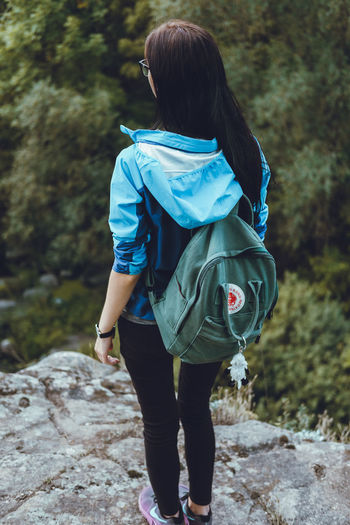 Adventure Backpack Casual Clothing Day Forest Full Length Hiking Leisure Activity Lifestyles Nature One Person Outdoors People Real People Rear View Standing Tree Walking Women Young Adult