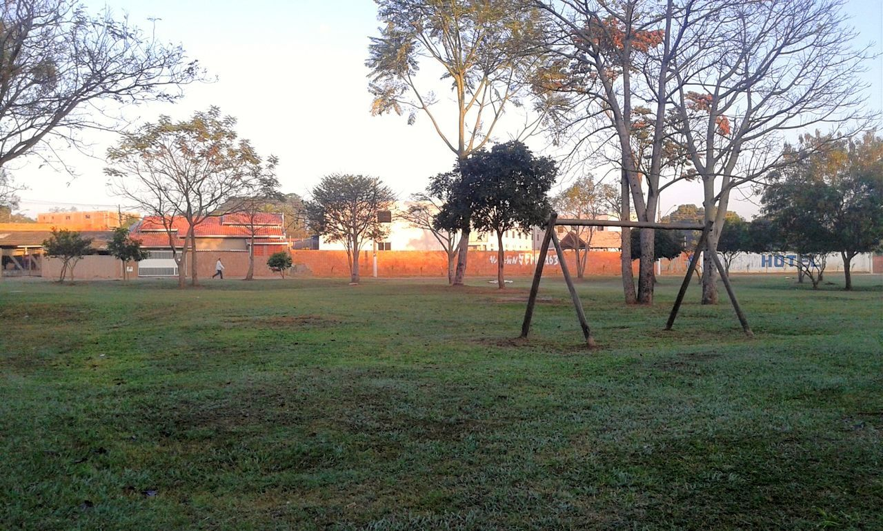 tree, playground, grass, field, bare tree, outdoors, day, green color, sky, outdoor play equipment, goal post, no people, nature, building exterior, architecture, beauty in nature