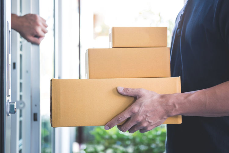 Midsection of delivery person giving cardboard boxes to man
