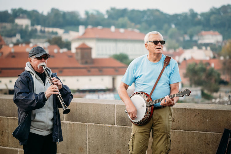 PRAGUE, CZECH REPUBLIC - OCTOBER 8, 2014: Street Buskers performing jazz songs on the Charles Bridge in Prague. Busking is legal form of earning money on Prague Streets. Trumpet Adult Charles Bridge City Czech Czech Republic Famous Jazz Man Music Prague Travel Art Busker Capital Culture Europe Guitar Instrument Old Outdoor People Perform Street This Is Aging