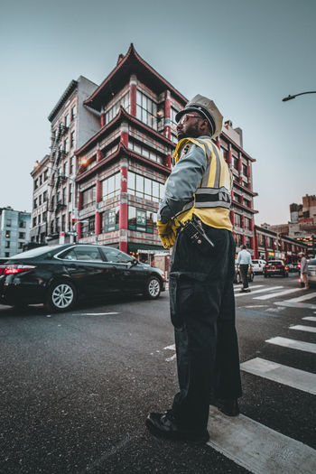 Man standing on road against sky in city