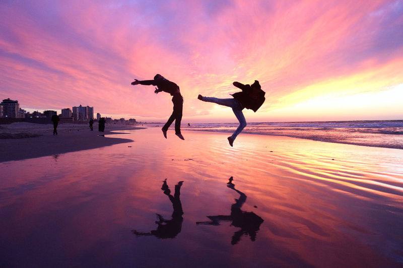 People jumping at beach against dramatic sky during sunset