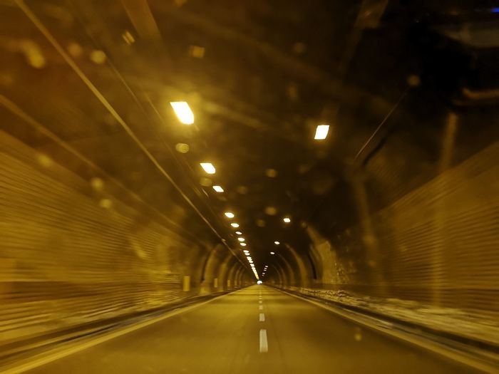 Empty road in illuminated tunnel