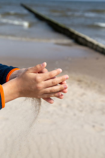 Midsection of person hand on beach