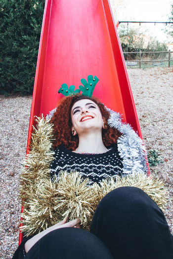 Portrait of smiling woman in slide at park