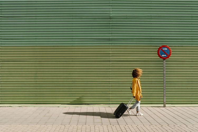 Full length of a boy walking on sidewalk