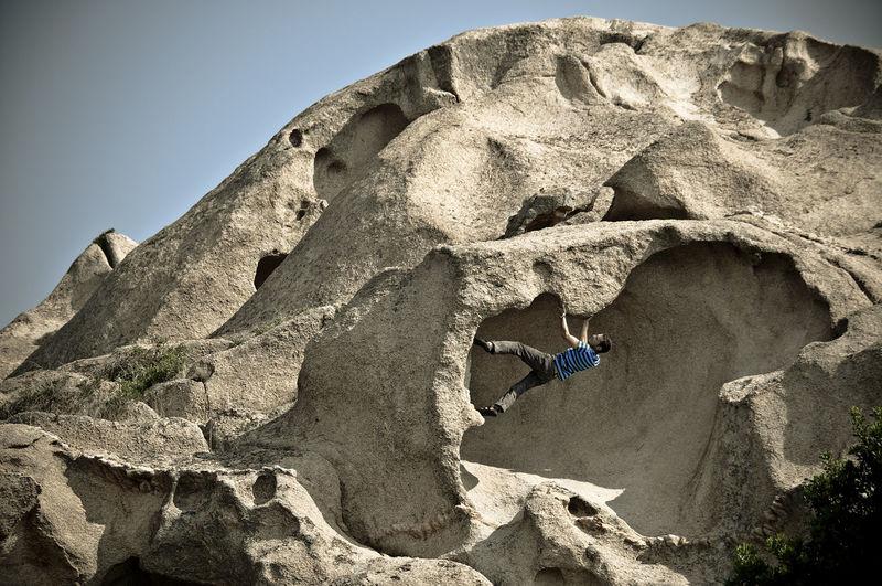 Man climbing on rock against sky