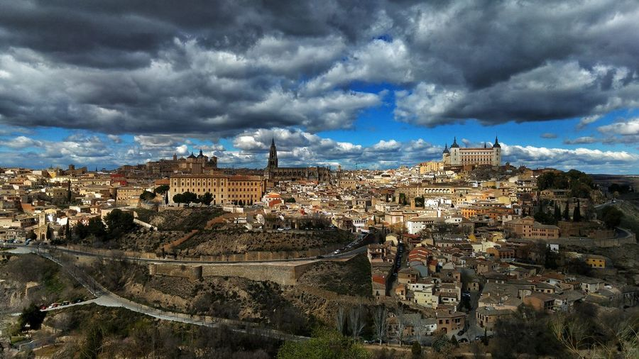 High Angle View Of Alcazar Of Toledo In City Against Cloudy Sky