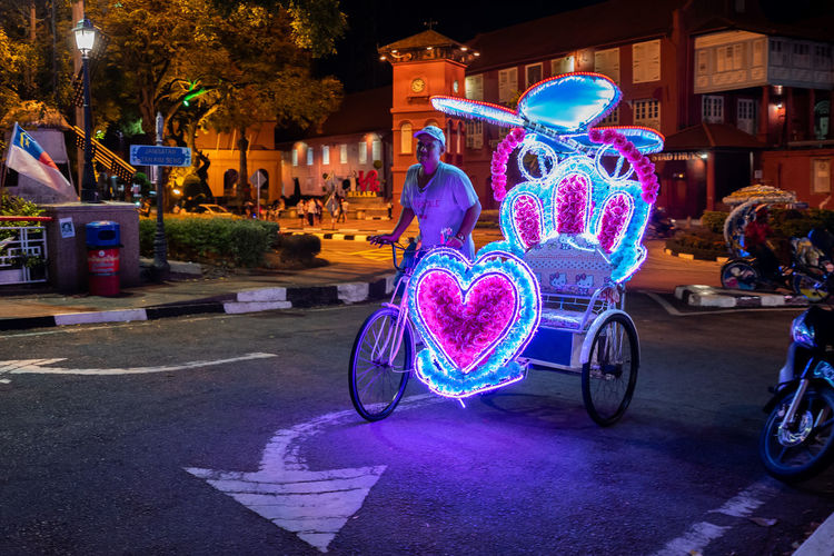 Malacca Transportation Illuminated City Street Mode Of Transportation Night Architecture Real People Road Building Exterior Land Vehicle Bicycle Incidental People Built Structure People Group Of People Adult Pink Color Men