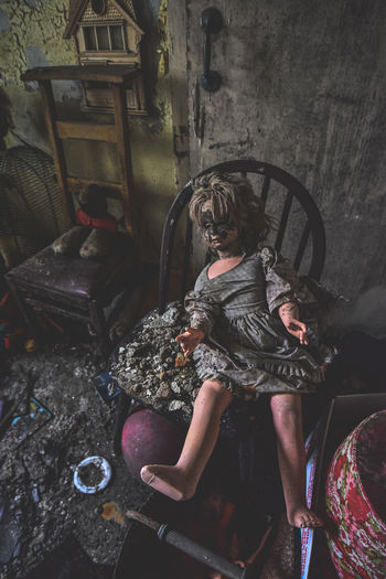 High angle view of doll on chair in abandoned building