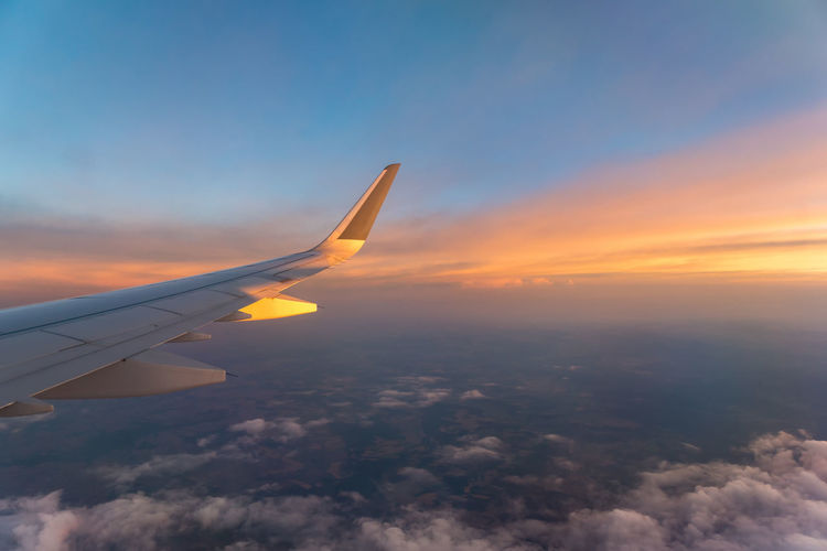 Aerial view of aircraft wing against sky during sunset