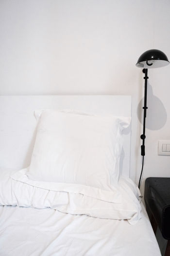 White electric lamp on bed against wall at home