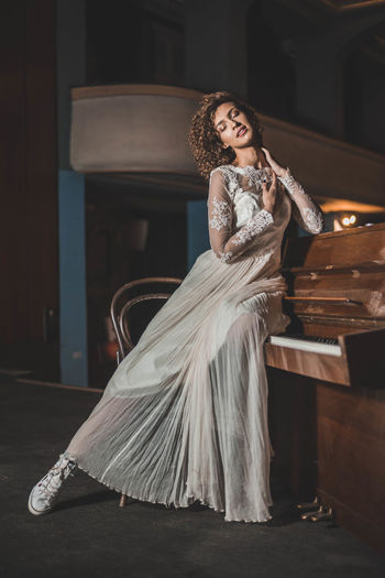 Full length of sensuous woman in white dress sitting on piano at home