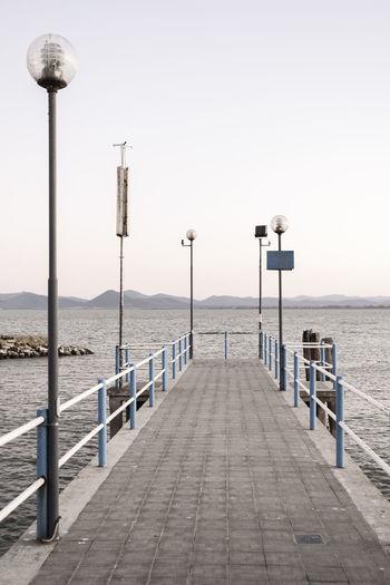 Street lights on pier by sea against clear sky