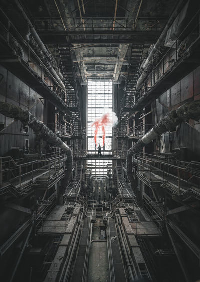 Full length of woman standing in factory with distress flare