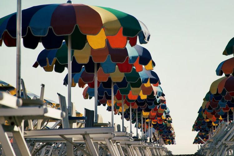 Low angle view of multi colored beach umbrellas hanging against sky