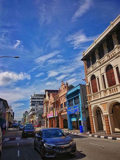 Buildings by road against blue sky in city