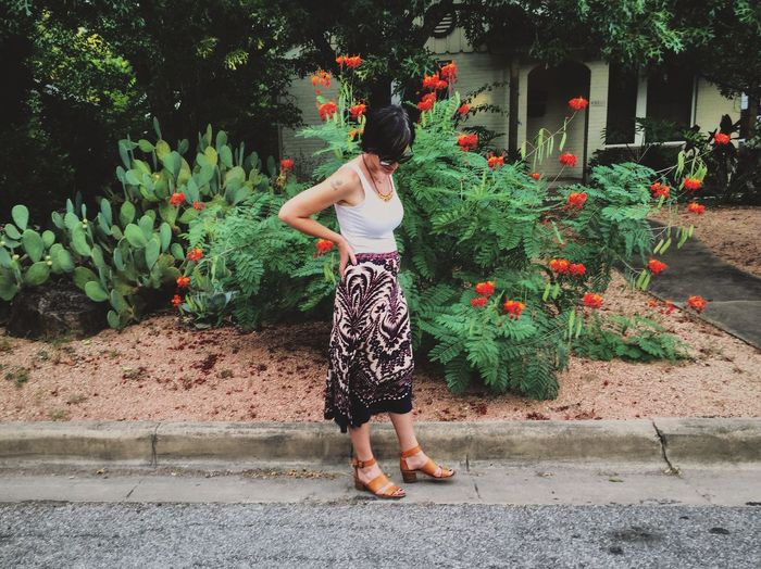 Full Length Of Woman Standing On Footpath By Plants