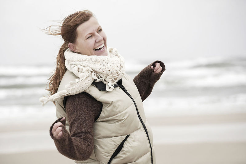 Portrait of smiling woman on beach against sky