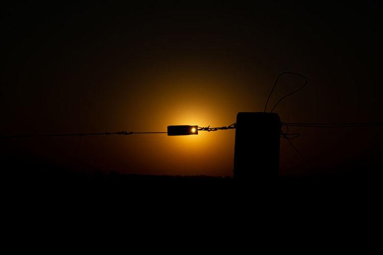 Silhouette light against orange sky