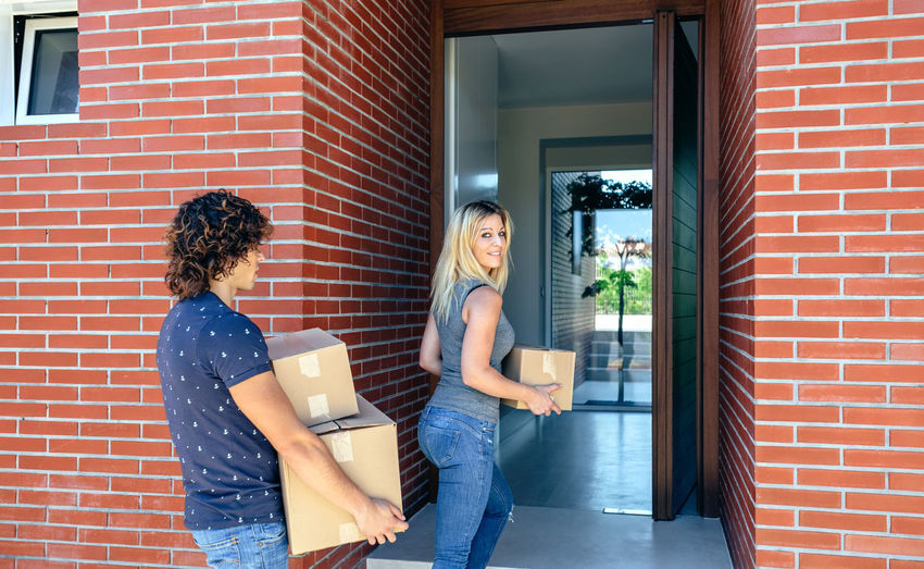 Couple taking cardboard boxes into home