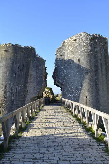 Bridge leading toward broken fort against clear blue sky