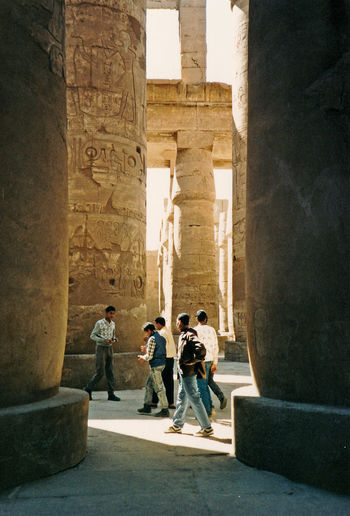 An Egyptian teacher talks to his pupils inside the Great Temple of Amun, Karnak, Luxor, Egypt Architecture People Real People Men Women Shadow Travel Tourism Statue Day History Outdoors Ancient The Past Archaeology Monument Adult Karnak Temple Full Length Egyptology Group Of People Travel Destinations Ancient Civilization Built Structure Old Ruin Architectural Column Stone Material Luxor, Egypt Temple Of Amun Egyptian Columns Ancient Egyptian Place Of Worship Hypostyle Hall, Karnak Pharoh Statues
