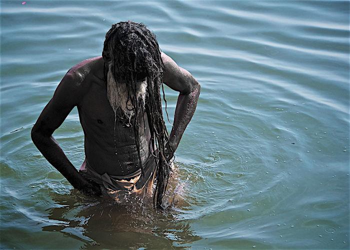 Rear view of shirtless man in lake
