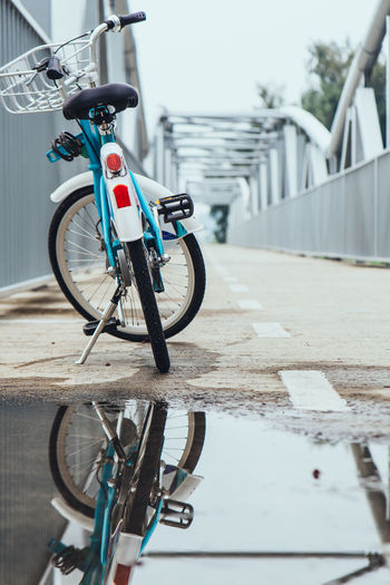 Bicycle Parked By Puddle On Bridge