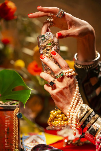 Gestures of a woman with jewelry, pearls, fruits and flowers. Abundance Wealth Celebration Art And Craft Mood Jewelry Gold Pearls Gesture Luxury Human Hand Hand Adult Human Body Part Women One Person Bracelet Focus On Foreground Close-up Bangle Fashion Ring Indoors  Holding Nail Pearl Jewelry Finger