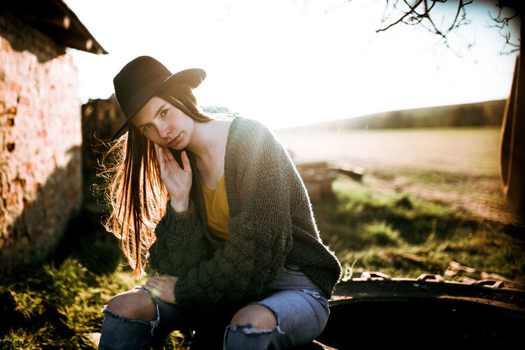 Young woman wearing hat while sitting on land