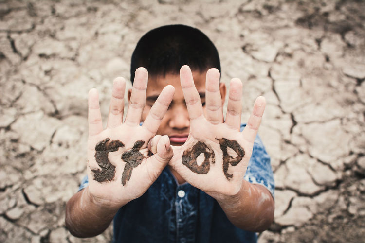 Boy with stop text on hands