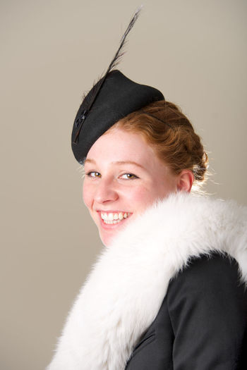Portrait of smiling young woman with fur against beige background