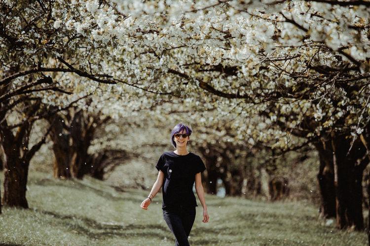 Full length of woman standing against trees
