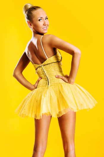 Beautiful ballerina in yellow tutu indoors Art Artist Ballerina Ballet Ballet Dancer Beautiful Woman Caucasian Choreography Dress Female Girl Grace Graceful Looking At Camera One Person People Professional Dancer Slim Studio Shot Yellow Background Young Adult Young Women