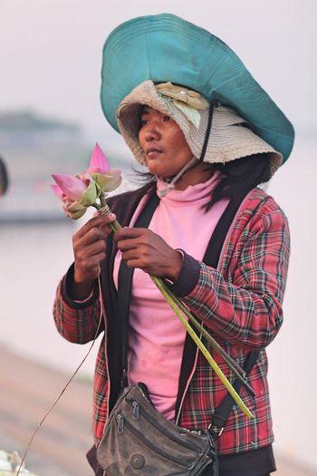 Woman Holding Lotus Flowers Against Sky