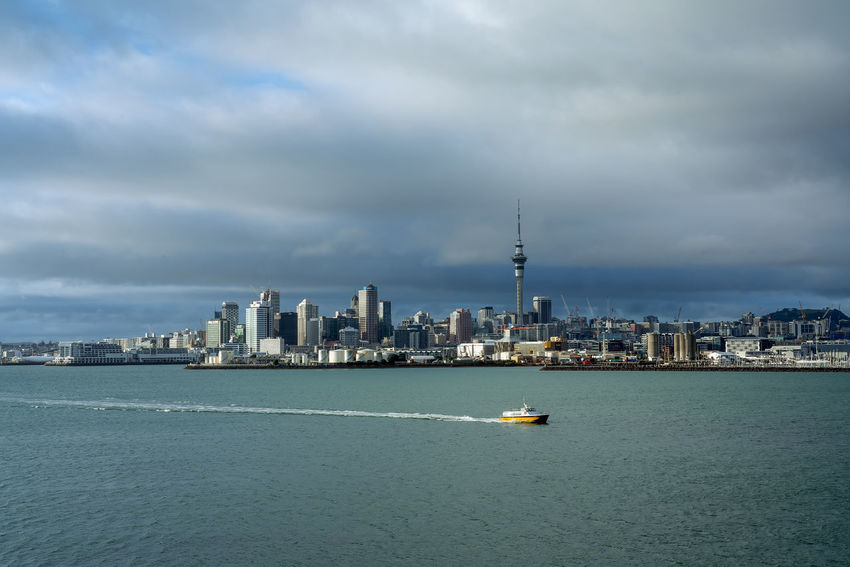 Auckland, New Zealand - August 20, 2018: Afternoon in Auckland, New Zealand. Architecture Built Structure Building Exterior Sky City Water Cloud - Sky Waterfront Building Cityscape Travel Destinations Travel Nautical Vessel Sea Nature Landscape Skyscraper No People Office Building Exterior Tall - High Outdoors Spire  Financial District  Clouds And Sky Auckland