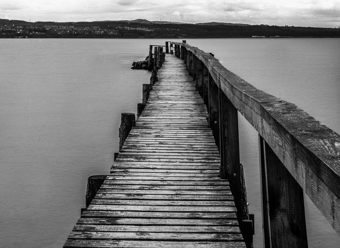 Tranquil scene with empty old wooden jetty on sea