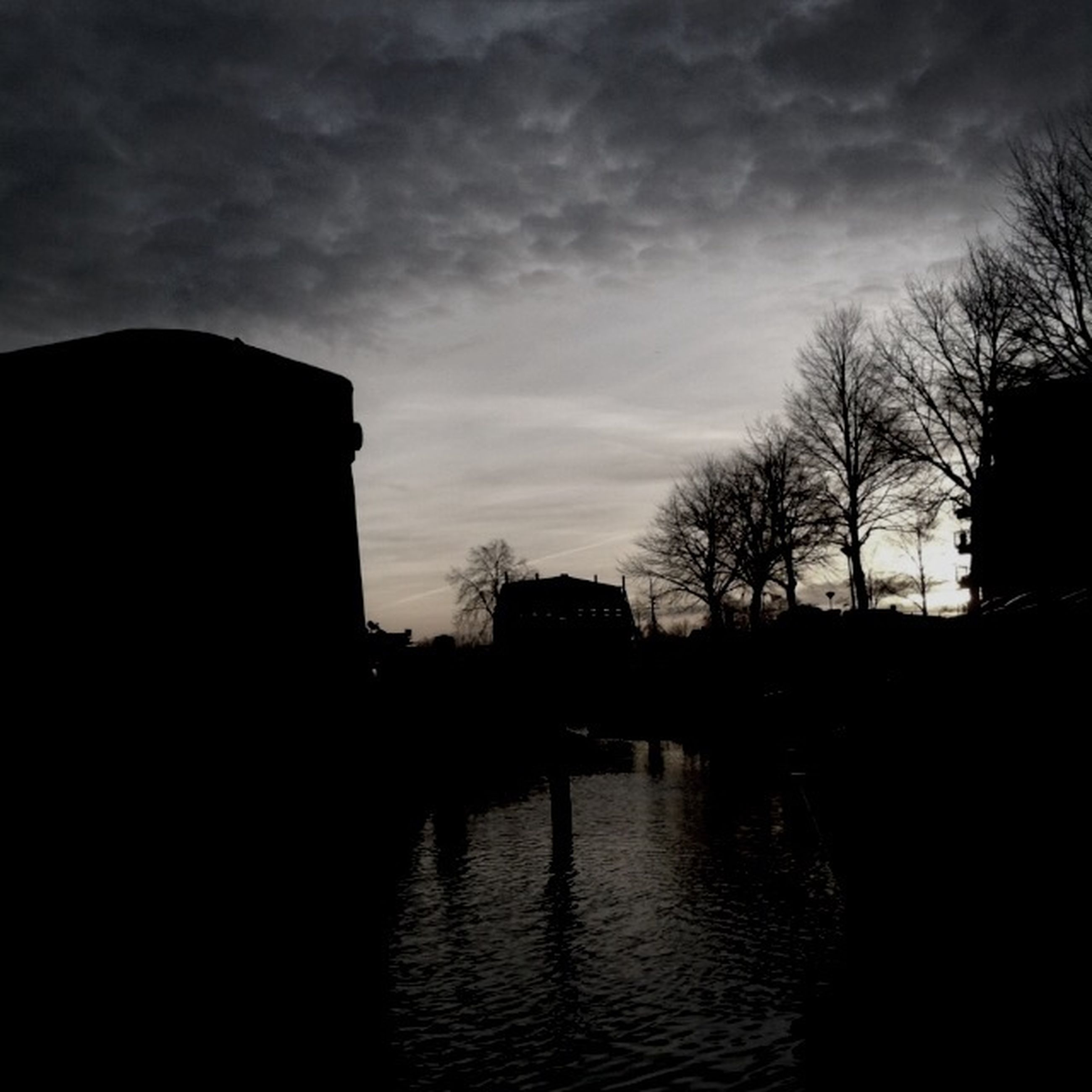 silhouette, sky, sunset, built structure, architecture, building exterior, cloud - sky, tree, water, cloud, river, waterfront, dusk, cloudy, dark, tranquility, nature, scenics, bare tree, tranquil scene
