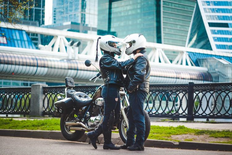 Motorcyclists embracing in city