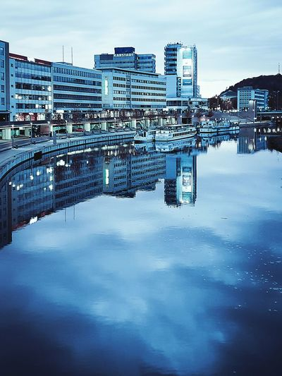 Reflection Of Buildings In Lake Against Sky