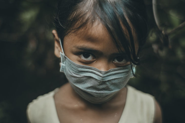 Close-up portrait of girl wearing mask standing outdoors
