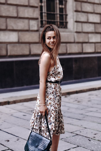 Young brunette woman in a long dress with black handbag smiling and posing on a street-style
