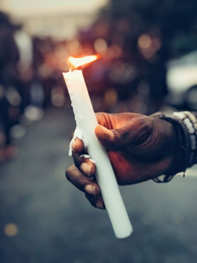 Close-up of hand holding burning candle outdoors