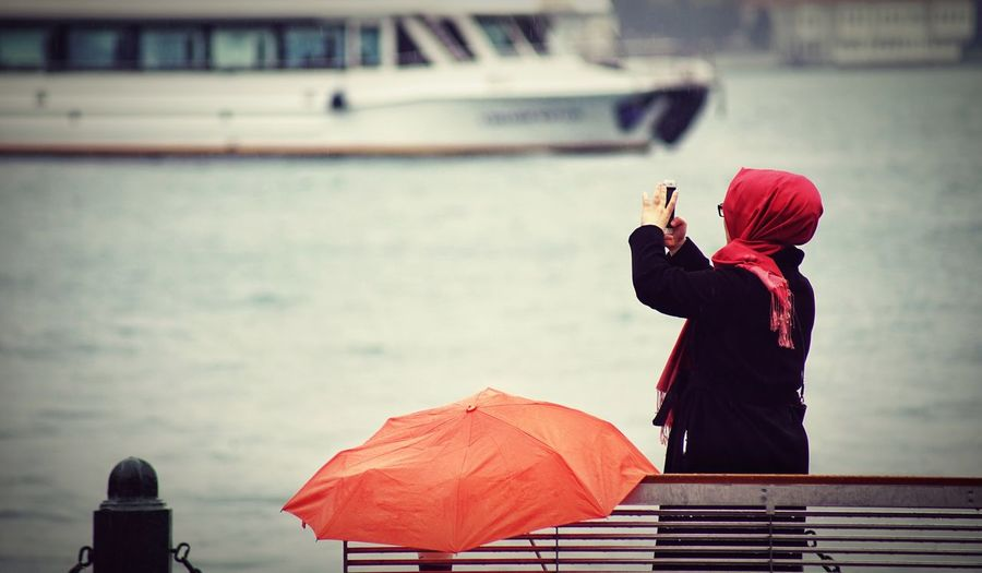 Side View Of Woman Photographing While Standing Against Sea
