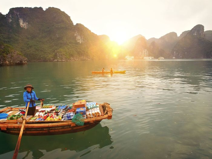 Vendor sailing on boat against mountains during sunset